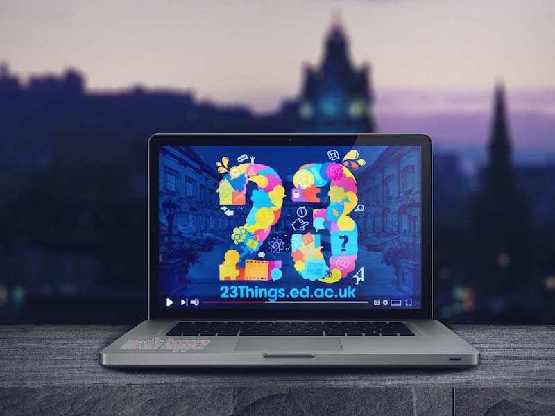 laptop with screen depicting the number 23, background skyline of Edinburgh city