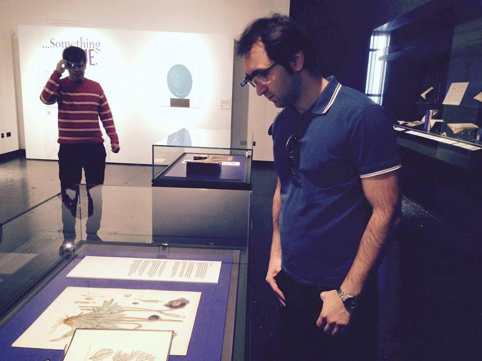 Man wearing Google Glasses looking at an exhibition case with documents