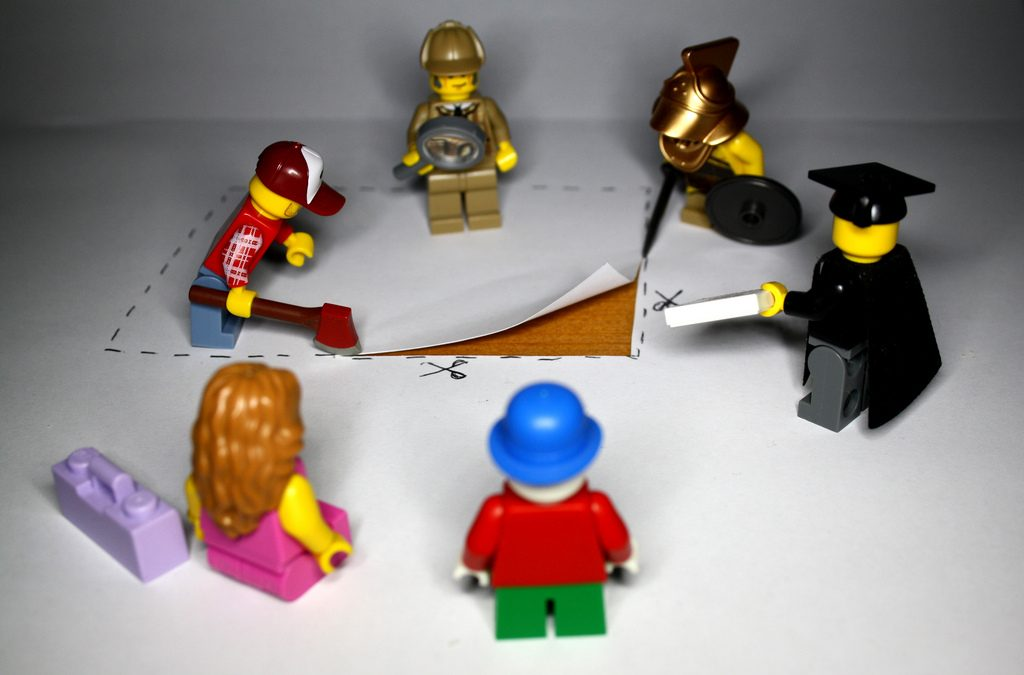 Lego figures, long haired woman in pink dress, scholar in hat and robe, sherlock holmes, investigate a square piece of cut paper.