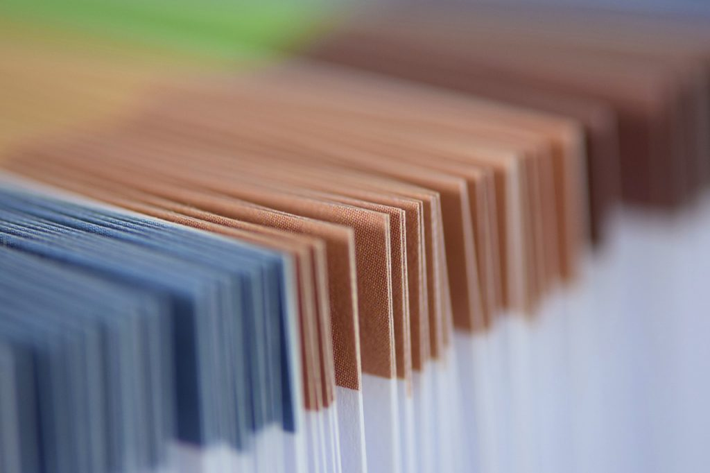 A row of white and blue, followed by white and brown, documents.