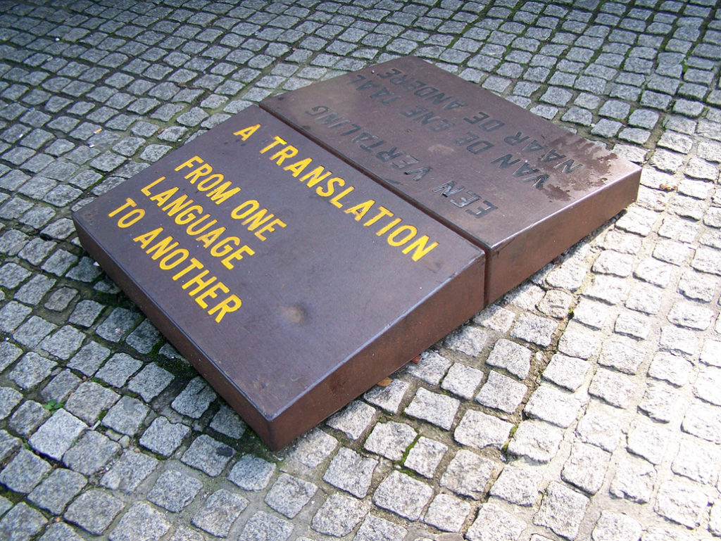 "The artwork ""Een vertaling van de ene taal naar de andere"" / ""A Translation from one language to another"" by Lawrence Weiner. Placed in 1996 at the Spui (square) in Amsterdam. It consists of three pairs of two stones placed against each other. On each stone there is an inscription ""A Translation from one language to another"", in another language - Dutch, English, Surinam and Arabic. Author: brbbl (CC-BY-SA)"